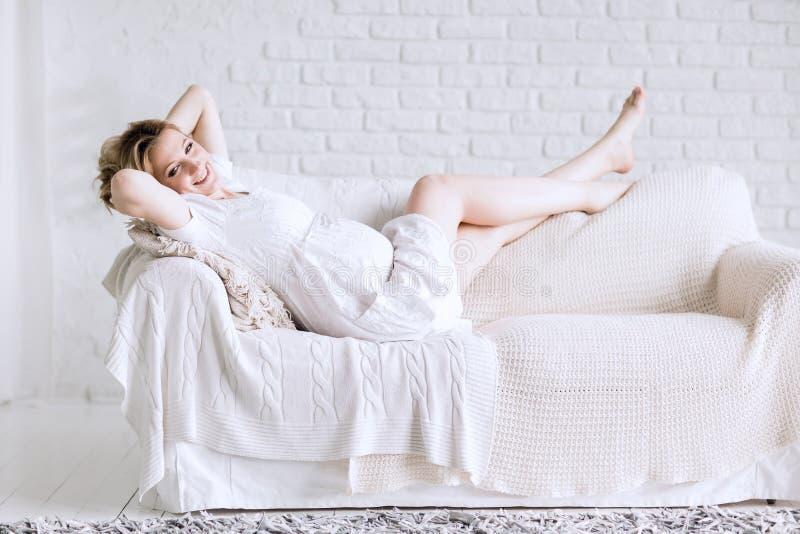 说谎在沙发的愉快的年轻孕妇在明亮的客厅 免版税库存照片