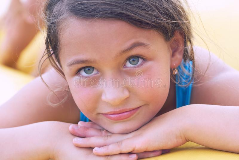 说谎在沙子的微笑的逗人喜爱的小女孩 在度假的系列 免版税库存照片