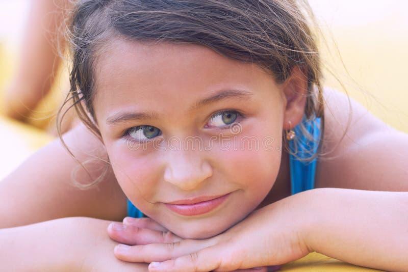 说谎在沙子的微笑的逗人喜爱的小女孩 在度假的系列 免版税库存图片