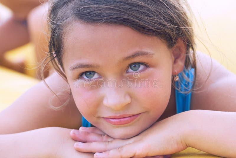 说谎在沙子的微笑的逗人喜爱的小女孩 在度假的系列 库存照片