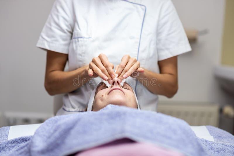 说谎在按摩书桌上的妇女享受皮肤护理治疗 库存照片