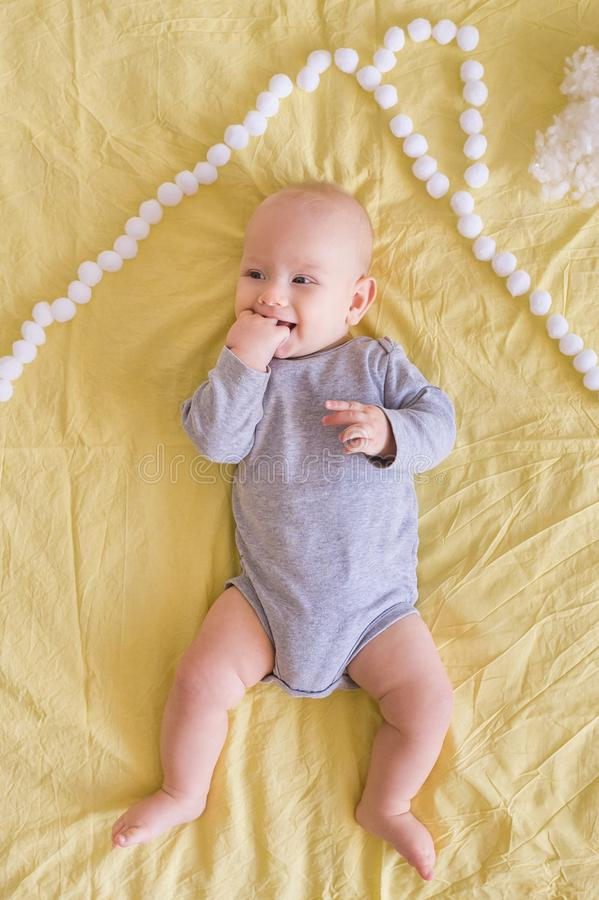 说谎在房子屋顶下的可爱的滑稽的婴儿顶视图由棉花球做成在床上 图库摄影