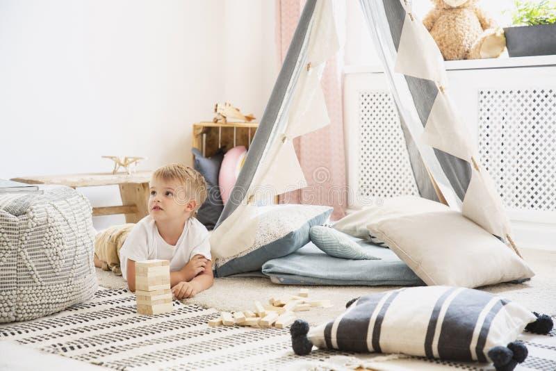 说谎在斯堪的纳维亚游戏室地板上的逗人喜爱的小男孩与灰色帐篷的有舒适枕头和被仿造的地毯的,真正的照片与 免版税图库摄影