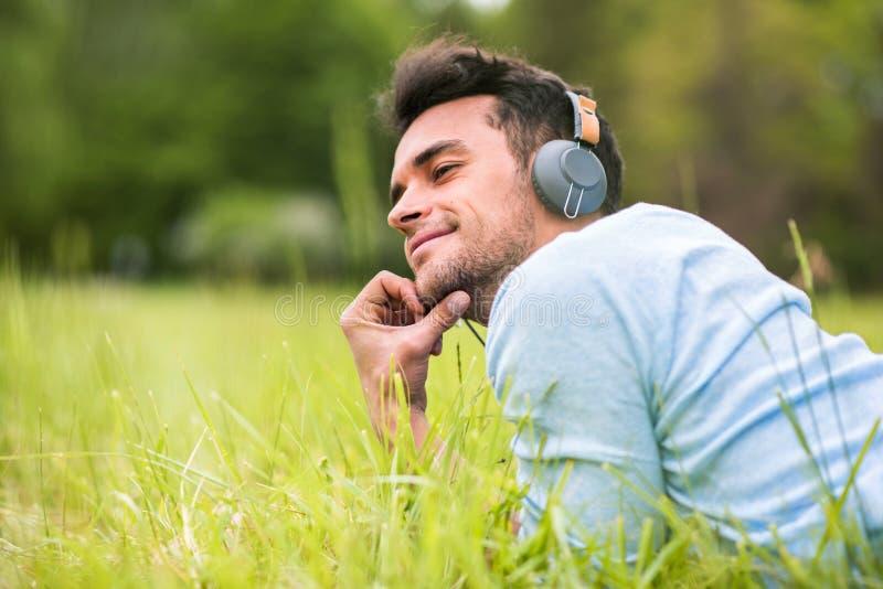 说谎在绿草的年轻人听音乐和神色从他的后面 图库摄影
