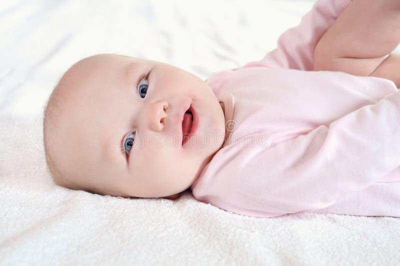 说谎在白色床单的一逗人喜爱的新生儿的画象 免版税库存照片