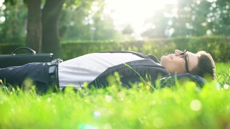 说谎在草和享受好日子,与自然的和谐的衣服的愉快的人 免版税库存照片