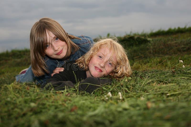说谎在草甸的两个女孩 免版税图库摄影