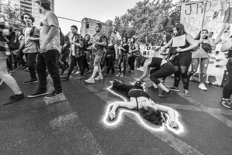 说谎在街道沥青的女孩抗议者在国际妇女节智利3月8日在圣地亚哥市中心街道, 免版税库存照片