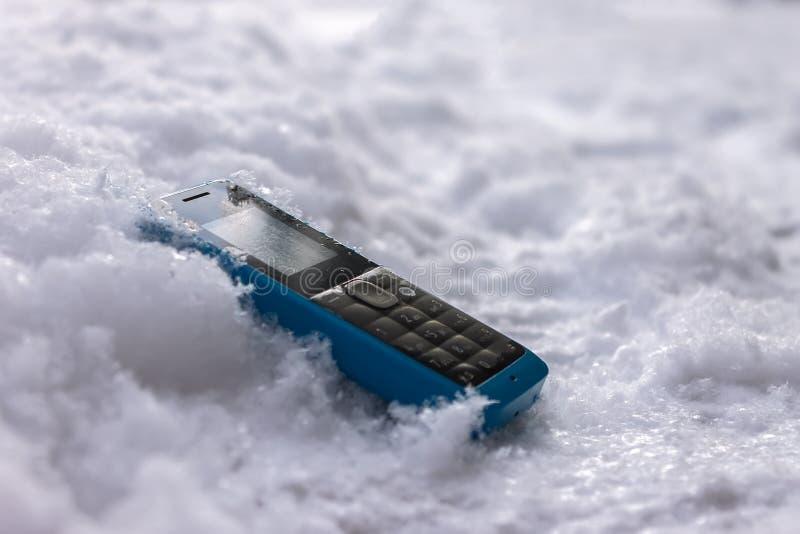 说谎在雪的路的失去的手机 免版税库存照片