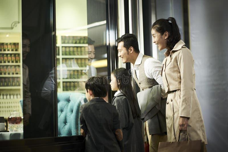 调查商店窗口的亚洲家庭 免版税库存照片