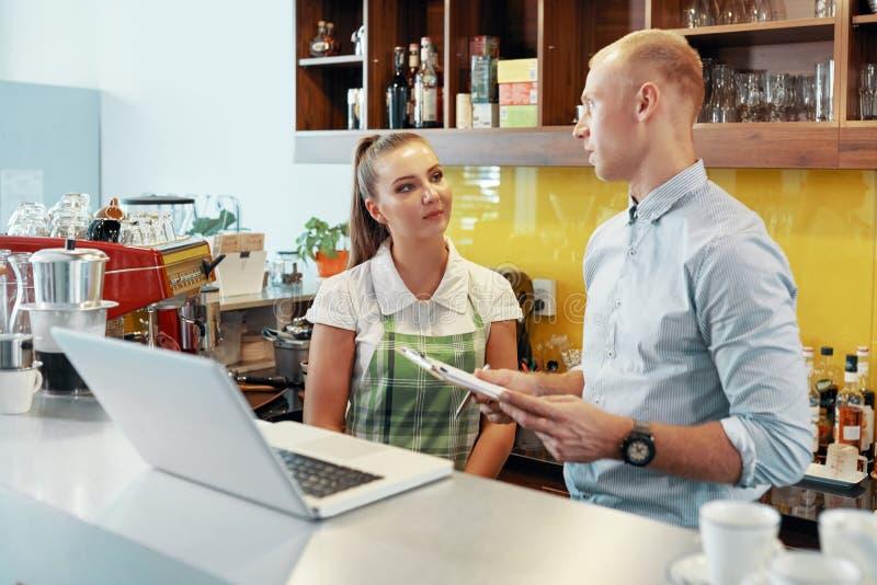 谈的饲槽和barista在咖啡馆 免版税库存照片