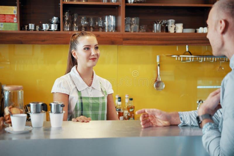 谈的barista和经理在咖啡馆 免版税库存照片