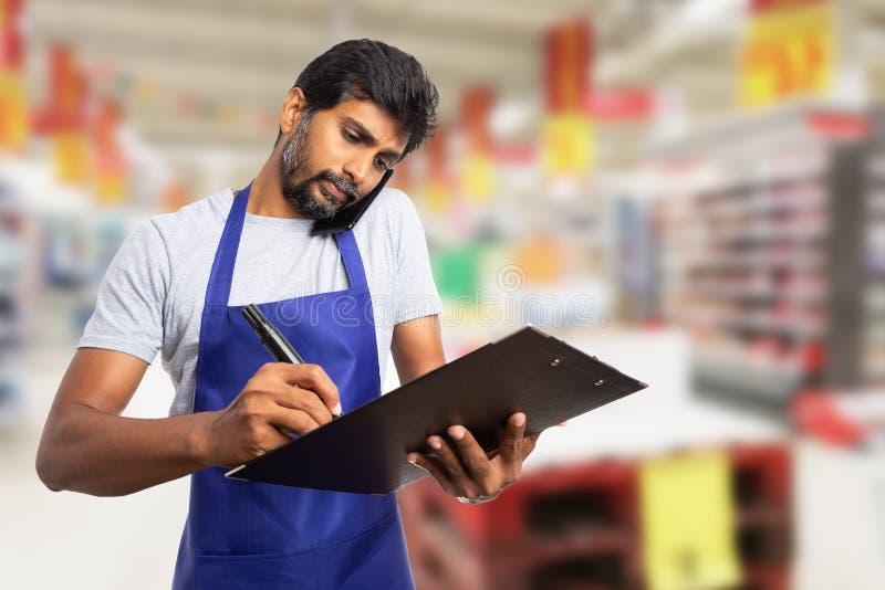 谈话在电话和采取笔记的大型超级市场雇员 库存照片