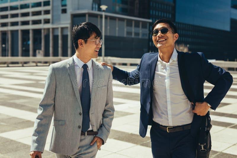 谈话和走在城市的两个微笑的商人 免版税库存图片