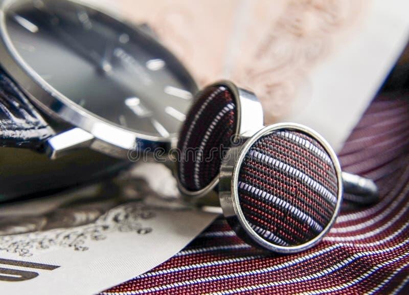 豪华人的手表和丝绸上漆的链扣和匹配衣服手帕和酥脆金钱笔记 库存图片