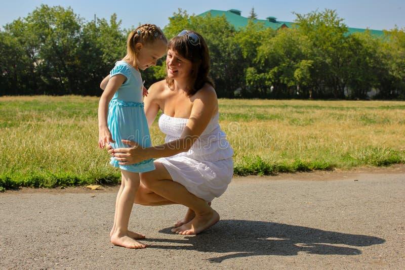 赤足女孩和母亲在沥青在夏天 库存图片