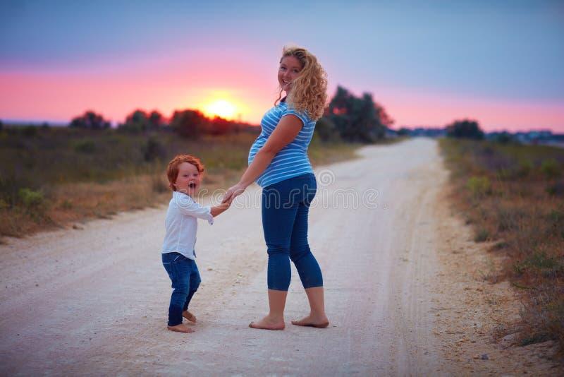 赤足走在乡下路的愉快的怀孕的母亲和小孩男婴在夏天日落 免版税库存照片
