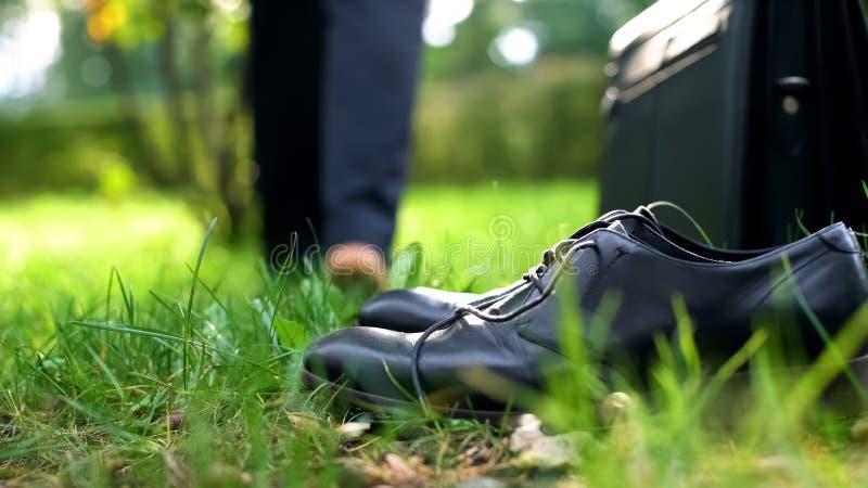 赤足走在绿草、鞋子和公文包的办公室工作者在前景 库存图片