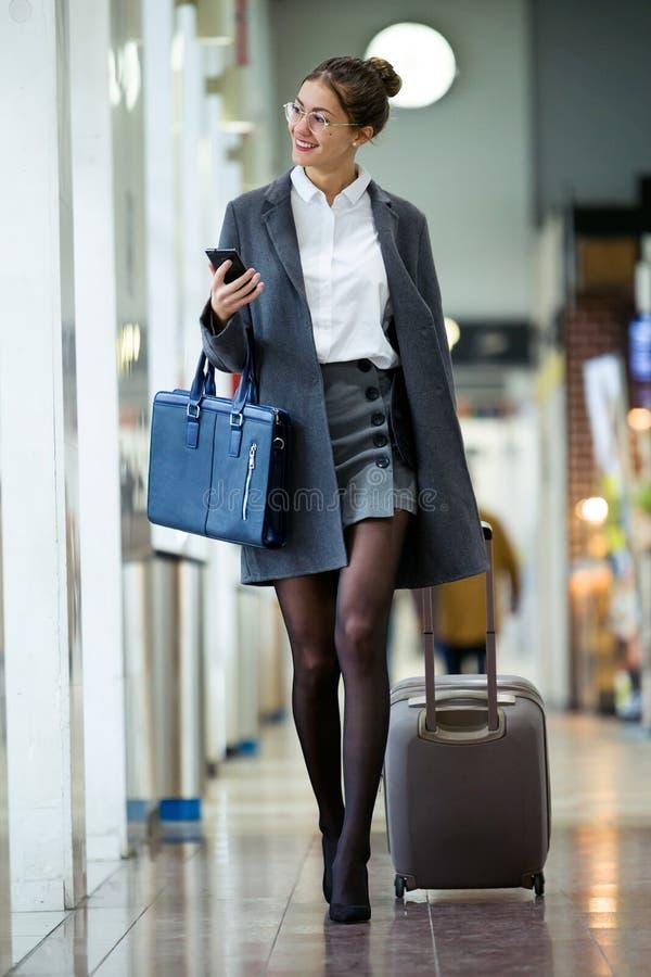 走带着手提箱的美丽的年轻女实业家,当拿着她的在大厅的手机火车站时 免版税图库摄影