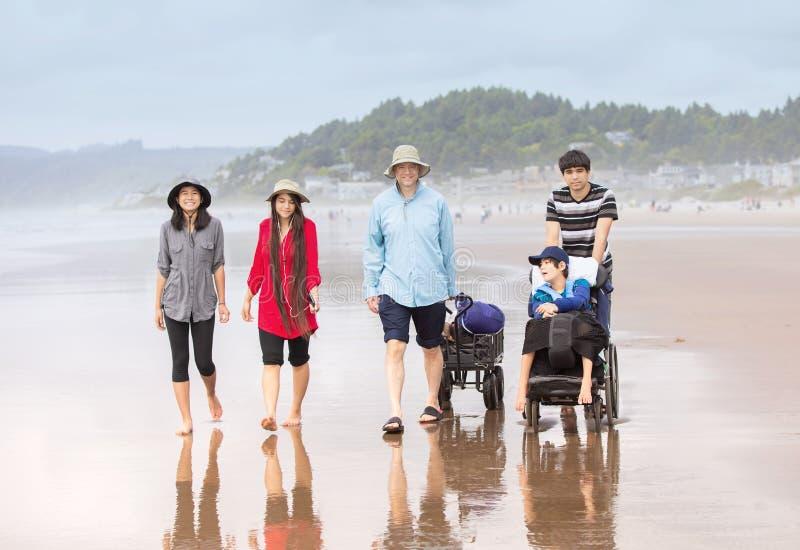 走在与残疾儿子的海滩的多种族家庭轮椅的 库存图片