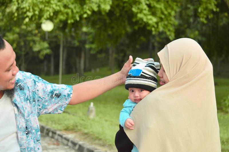 走在室外公园的愉快的穆斯林的家庭抱着一个婴孩及时白天 库存照片