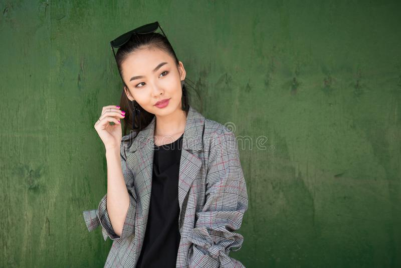 走在城市街道佩带的夹克和太阳镜的美丽的年轻亚裔时装模特儿妇女 图库摄影