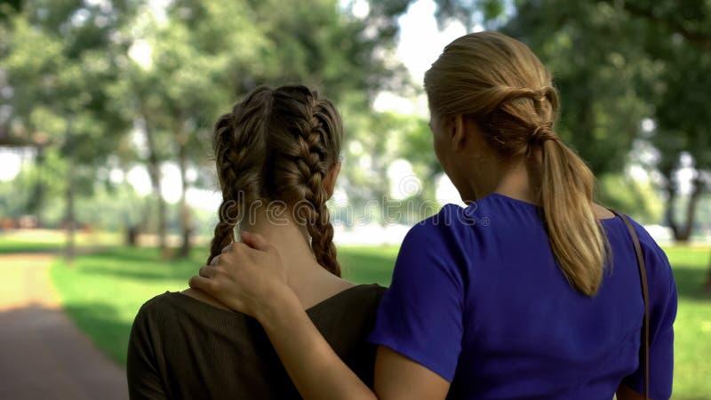 走在公园,交谈的后面观点的妈咪和女儿关于生活,劝告 图库摄影