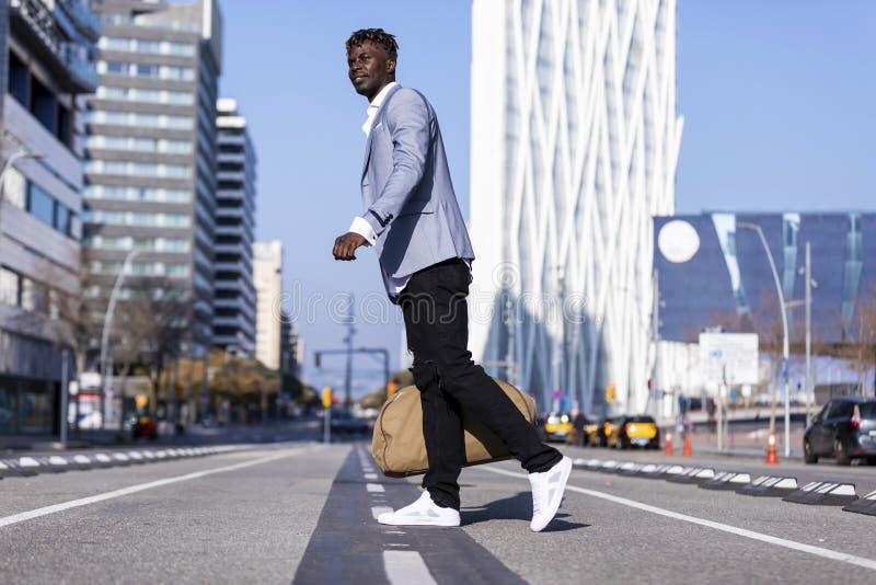 走在街道上的一个典雅的年轻非洲黑人人的侧视图运送袋子,当看户外时 免版税图库摄影