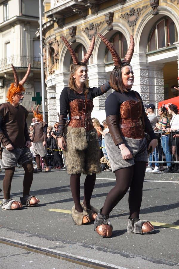 走在街道的年轻人掩没在神在狂欢节队伍的平底锅服装 库存图片