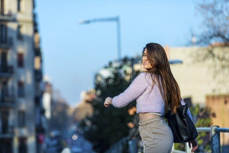走在街道的微笑的美丽的年轻女人背面图,当看回到照相机在一好日子时 库存照片
