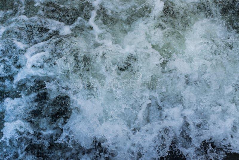 起泡沫的水在一条冲的河 库存图片