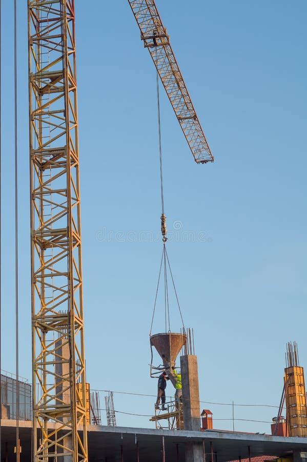 起重机工作 在建筑的起重机降低了混凝土给工作者 免版税库存照片