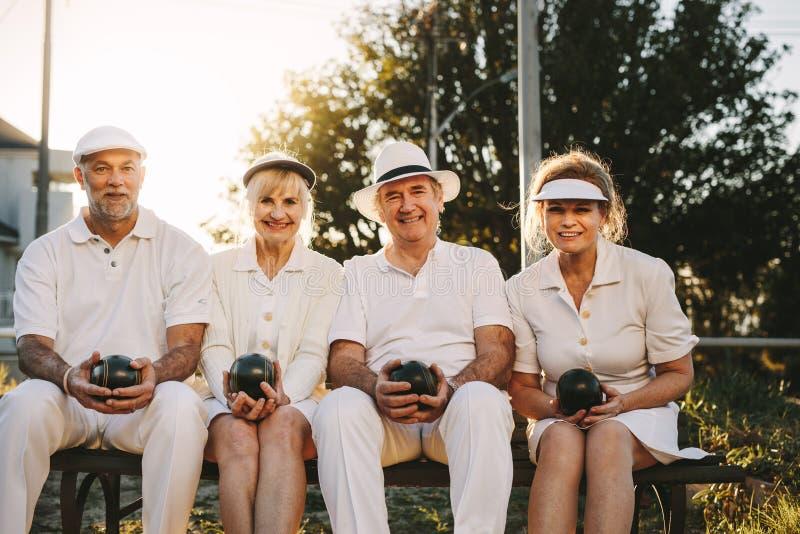 资深人民一起坐一条长凳在拿着boul的公园 库存照片
