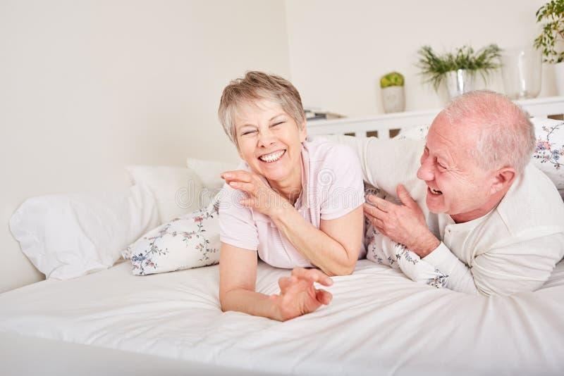 资深夫妇获得乐趣在卧室 免版税库存照片