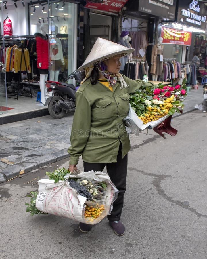 越南摊贩在河内,走横跨街道运载的花卖在每只手上 图库摄影
