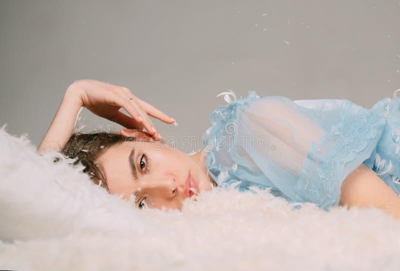超轻和易上手 放松在羽毛床垫枕头和床垫的逗人喜爱的女孩 睡眠穿戴的年轻女人 相当 免版税库存照片
