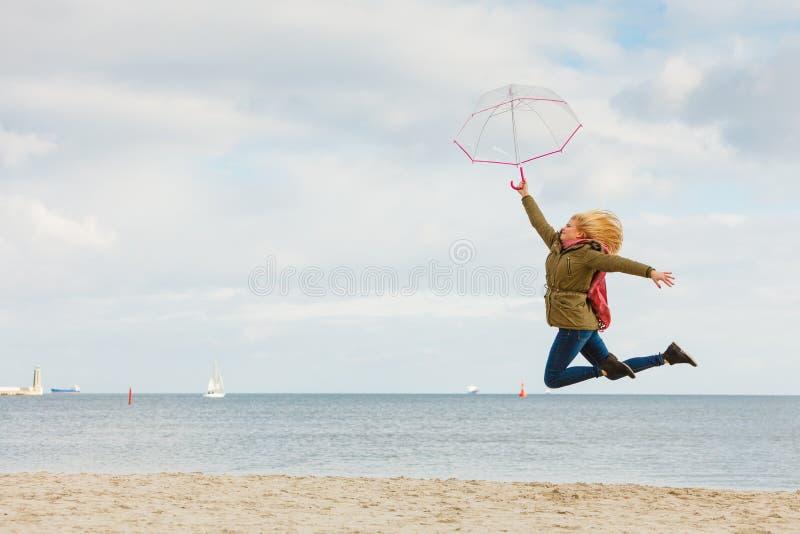 跳与在海滩的透明伞的妇女 免版税图库摄影