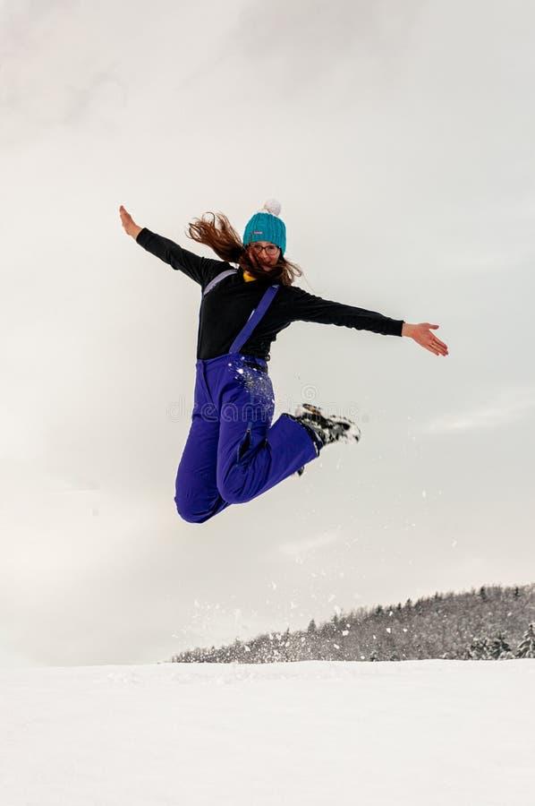 跳在雪的女孩 免版税库存图片