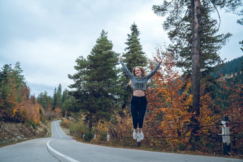 跳跃为在路的喜悦的美丽的少女在Svaneti 库存图片