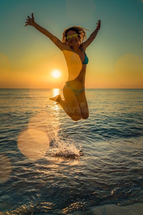 跳跃在海的愉快的妇女 免版税图库摄影