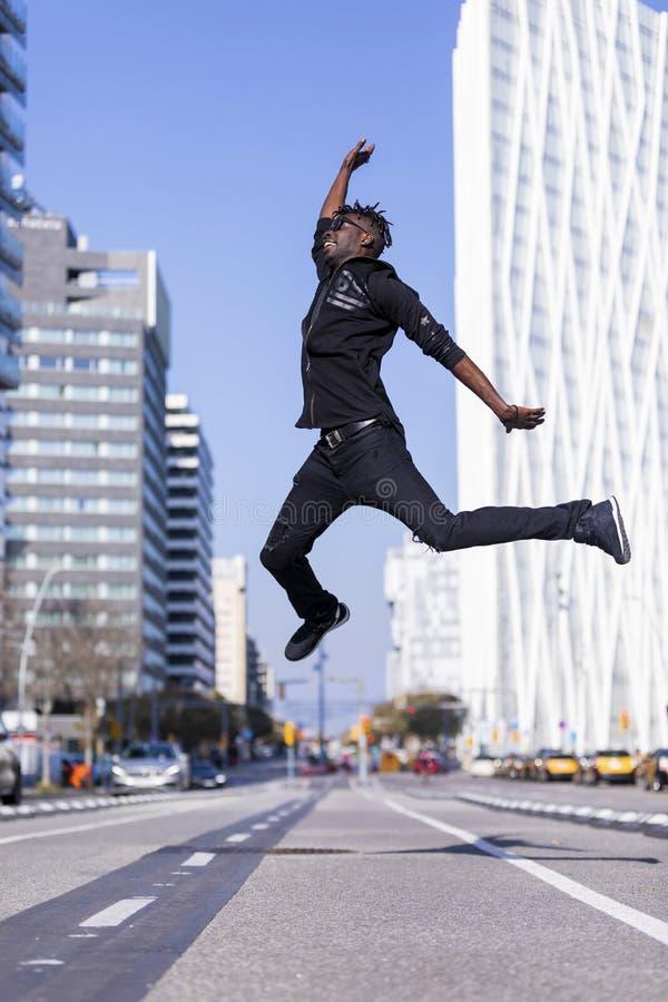 跳跃在都市背景中的侧视图年轻黑人佩带的便服 生活方式概念 千福年非洲人佩带 免版税库存照片