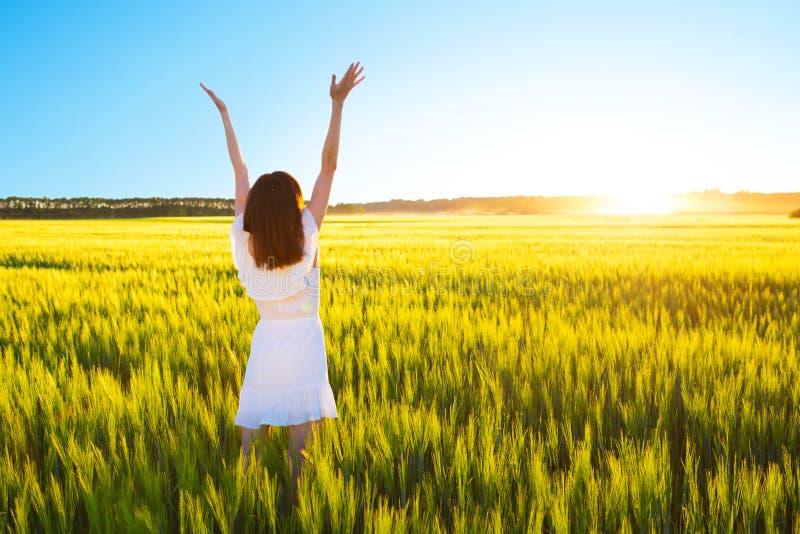 跳跃用被举的手的白色礼服的美丽的白种人妇女室外 领域用黄色麦子 免版税库存图片