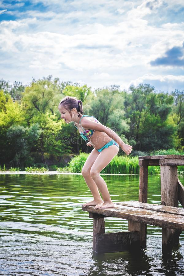跳跃船坞的小逗人喜爱的女孩入一条美丽的河在日落 免版税库存照片