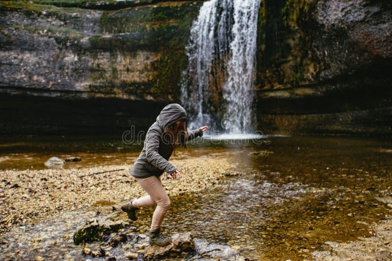 跳过在瀑布前面的石头的妇女 Cascades du HA©rissonn,法国 库存照片