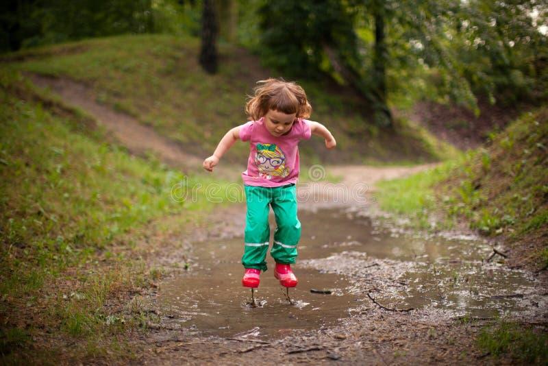 跳进水水坑的孩子 库存照片