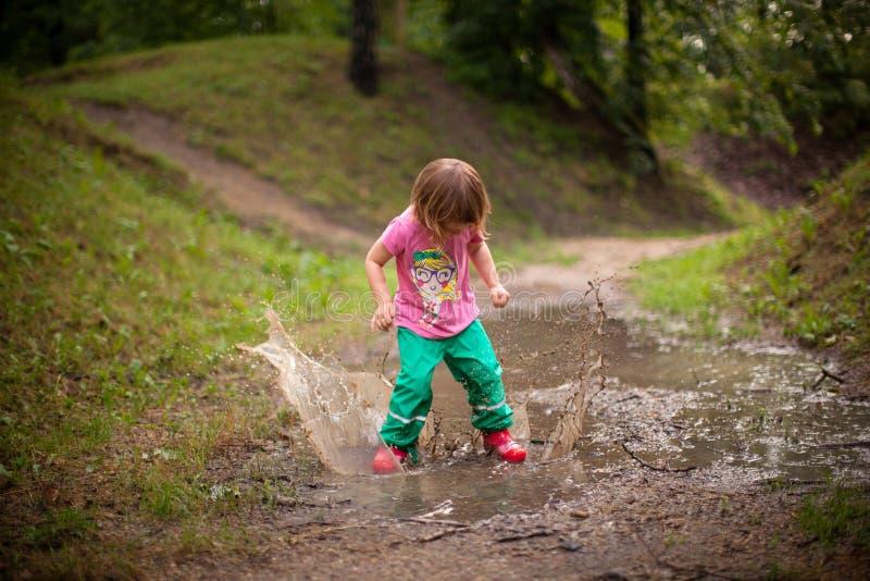 跳进水水坑的孩子 免版税库存照片