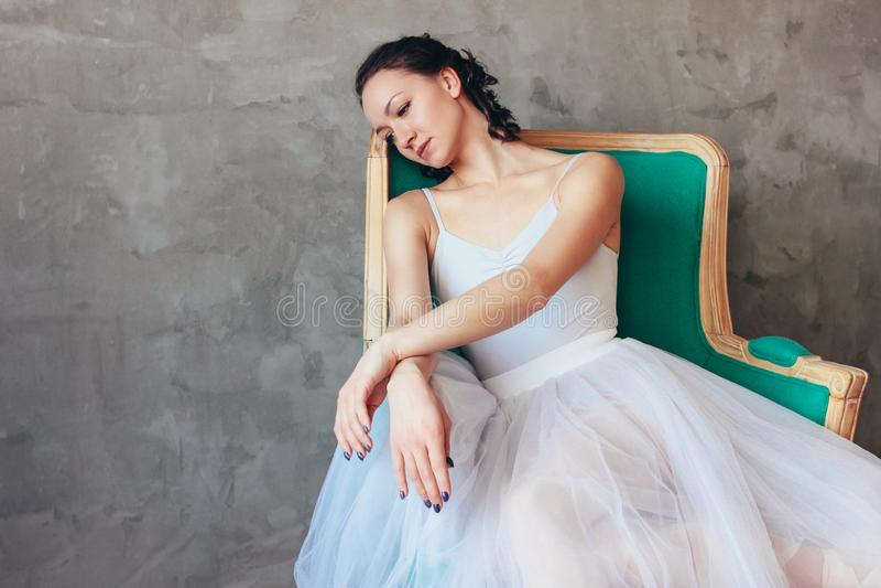 跳芭蕾舞者芭蕾舞女演员坦率的画象摆在vinage椅子的美丽的浅兰的礼服芭蕾舞短裙裙子的开会在顶楼演播室 免版税库存照片
