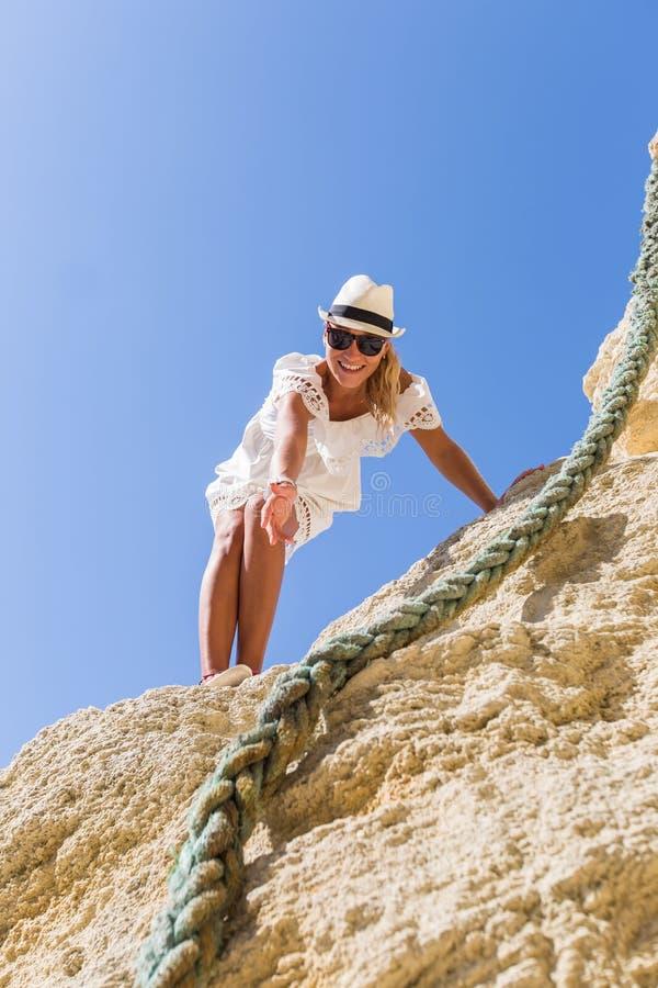跟我学!女孩在岩石站立并且提供援助她的手 库存照片
