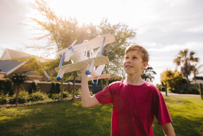 跑与玩具飞机的年轻男孩 库存照片