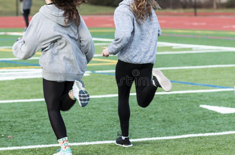 跑在实践onn草皮领域的两个女孩 库存图片